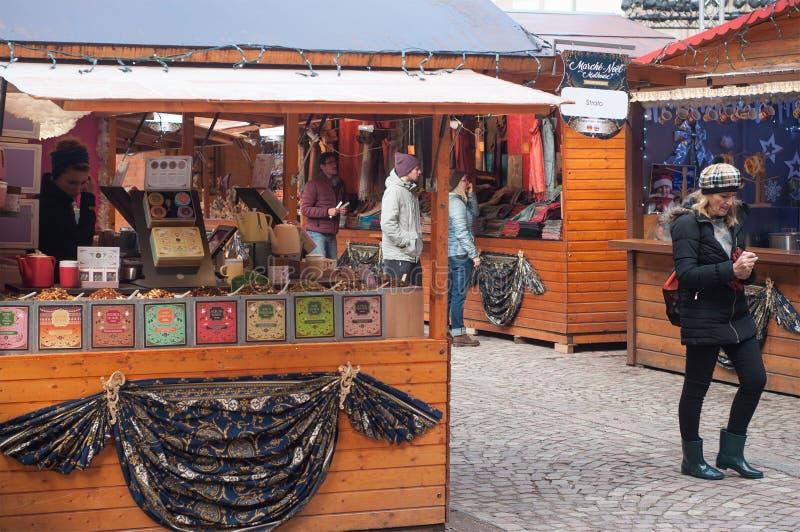 Les gens marchant au marché de Noël devant le thé font des emplettes image libre de droits