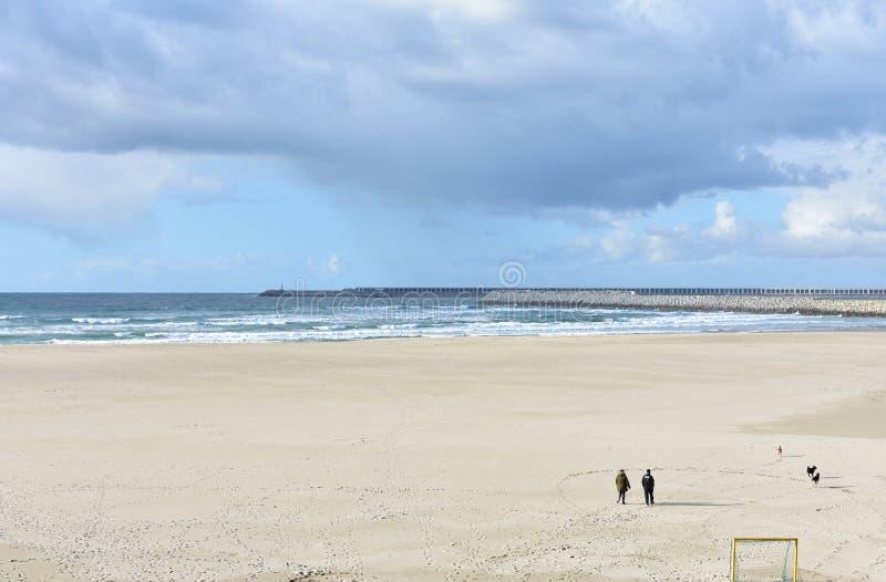 Les gens marchant avec des chiens sur une plage avec le port jour nuageux Sabon, Espagne le 2 février 2019 image stock
