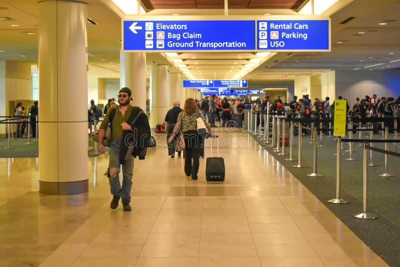 Les gens marchant dans l'enregistrement et étiquetant le secteur chez Orlando International Airport 1 photo stock