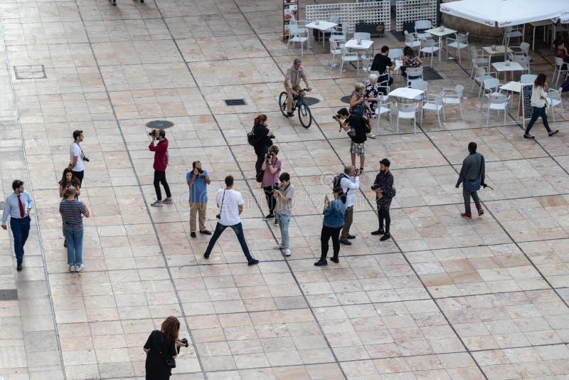 Les gens marchant et prenant des photos sur une grande place photos libres de droits
