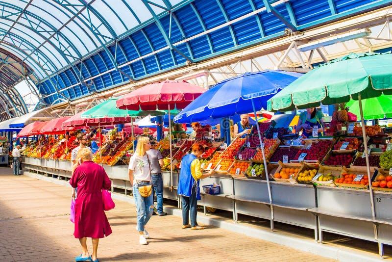 Les gens marchant le long des rangées du marché, achetant des fruits et légumes images stock