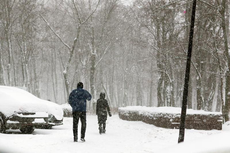Les gens marchant par la rue de ville couverte de neige pendant les chutes de neige lourdes Tempête de neige dans la ville à l'hi photographie stock libre de droits