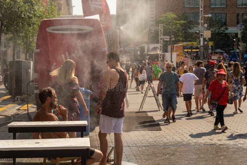 Les gens marchant sous le système de brouillard pour refroidir pendant la vague de chaleur photographie stock libre de droits