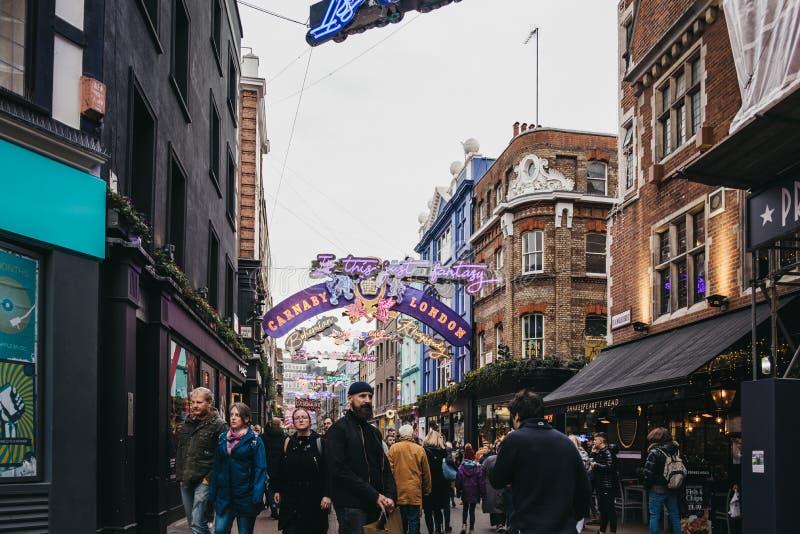 Les gens marchant sous les lumières de Noël orientées de rhapsodie de Bohème dans le Carnaby Street, Londres, R-U photos stock