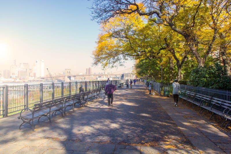 Les gens marchant sur Brooklyn Heights promenade avec la vue de Manhattan images libres de droits