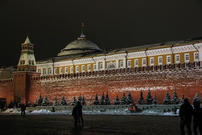 Les gens marchant sur la place rouge la nuit près du mausolée de Lénine en hiver images stock