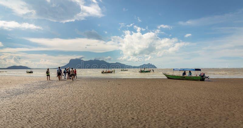 Les gens marchant sur la plage pour obtenir aux bateaux de retourner du parc national de Bako au Bornéo photos libres de droits