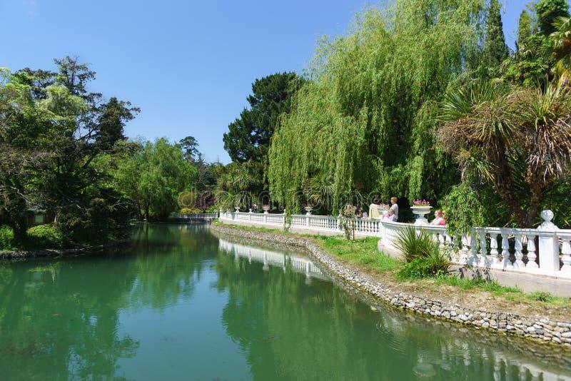 Les gens marchent autour de l'étang en vieux parc L'étang est clôturé avec une balustrade blanche image stock