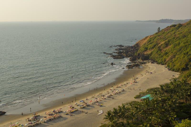 Les gens marchent le long de la plage sablonneuse, détendent sur un canapé et se baignent en mer, près des roches et de la paume photo stock