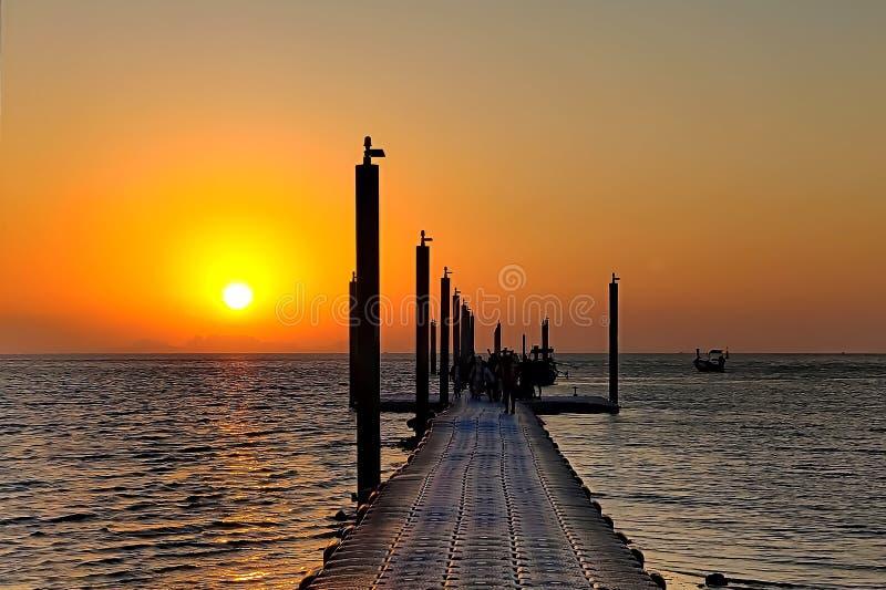 Les gens marchent le long du pilier à la plage au lever de soleil Travailleurs navigués sur des bateaux photo stock