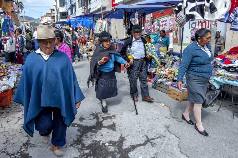Les gens marchent passé les nombreuses stalles au marché indien dans Otavolo en Equateur photographie stock libre de droits