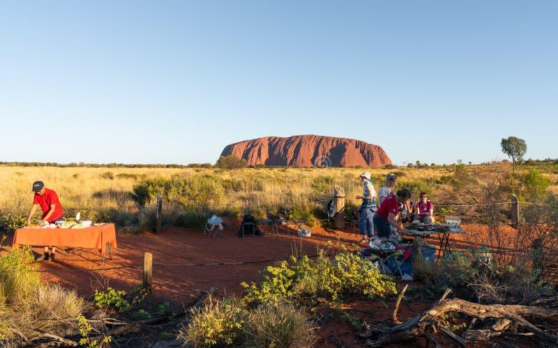 Les gens mettant des tables de buffet de BBQ de dîner au point de vue de coucher du soleil d'Uluru et à la roche d'Ayers à l'arri image libre de droits