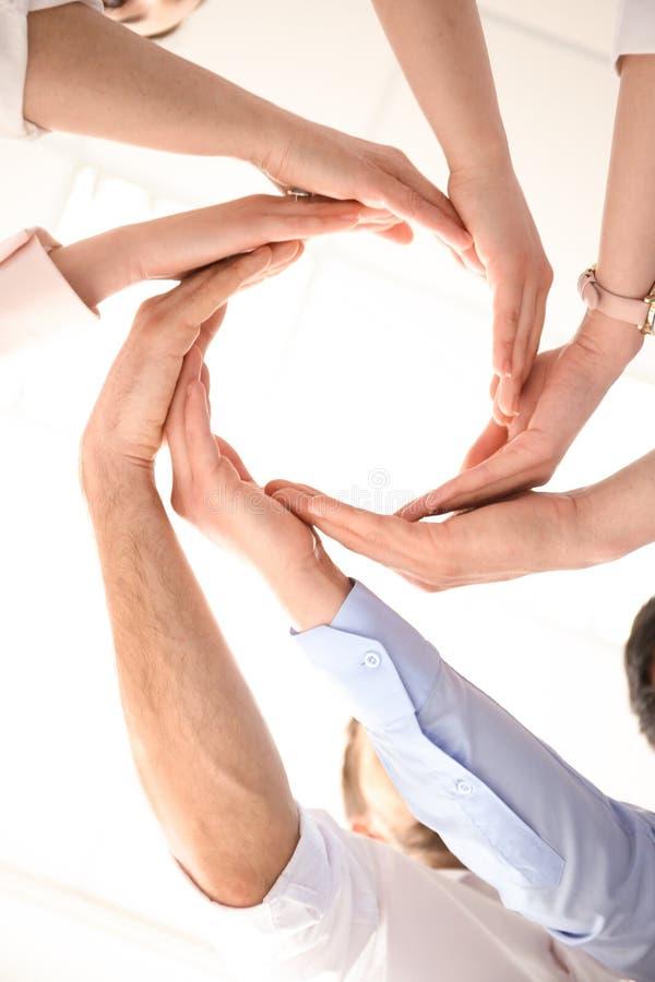 Les gens mettant leurs mains dans le cercle sur le fond clair photographie stock libre de droits