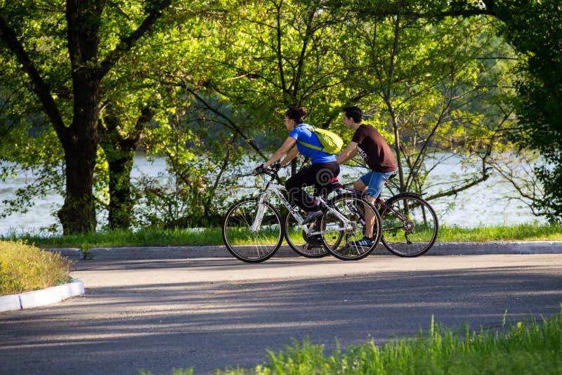 Les gens montant sur les bicyclettes dans la ville se garent image stock