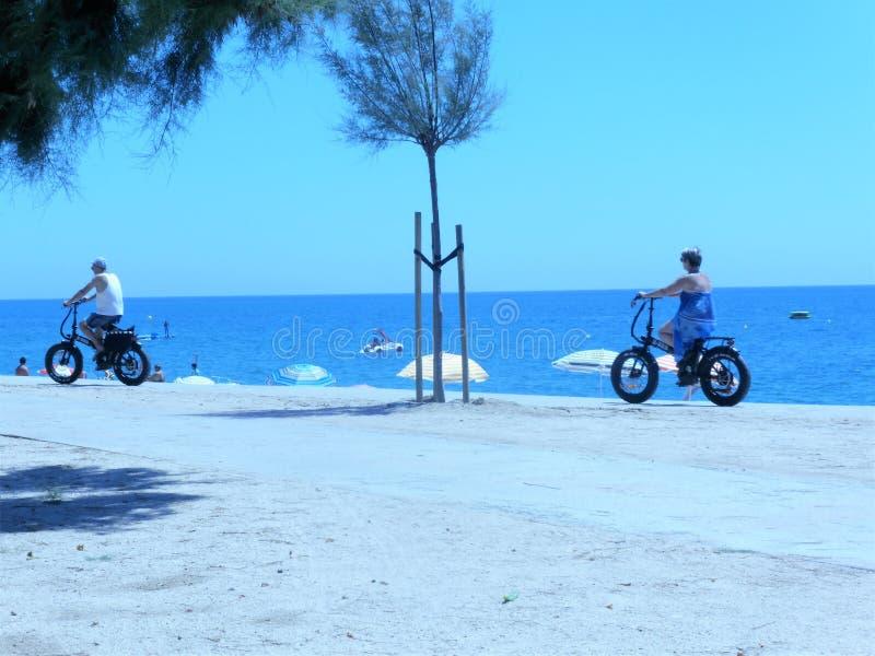 Les gens montant les vélos électriques sur la plage photo libre de droits