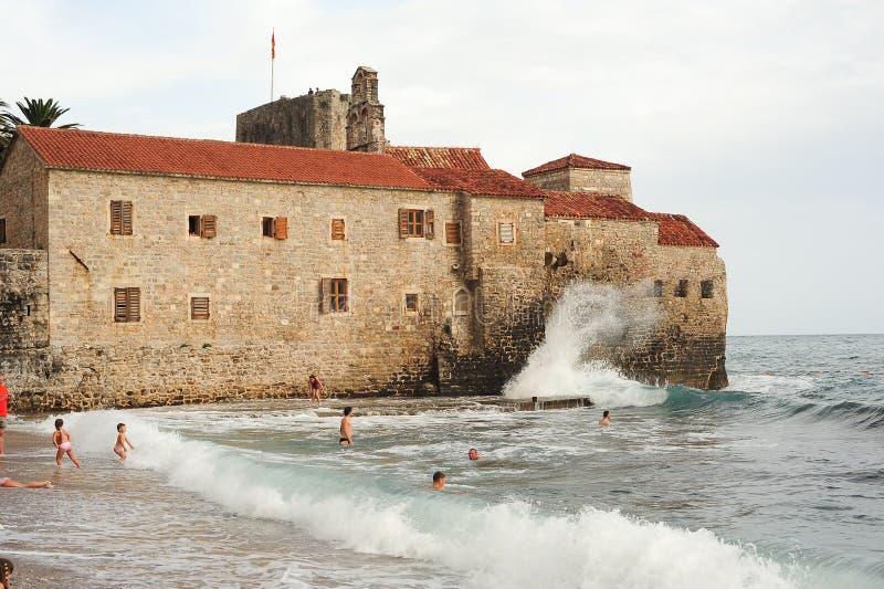 Les gens nageant sur les vagues de l'océan devant le citade images libres de droits