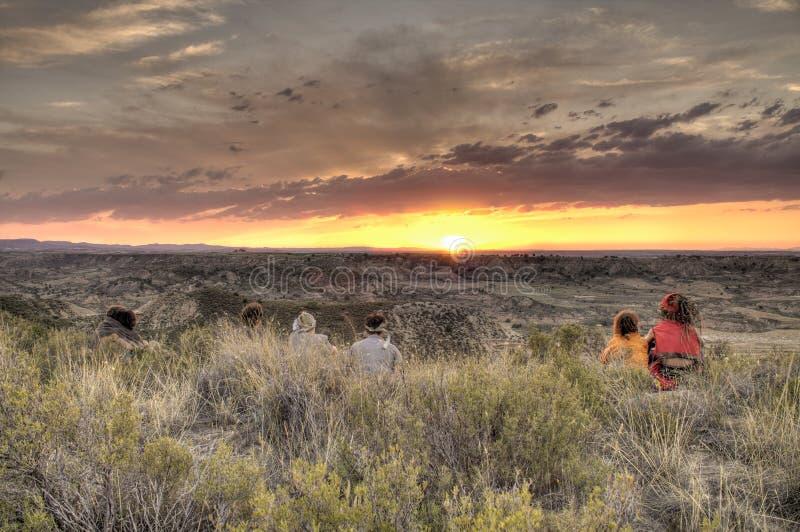 Les gens observant un coucher du soleil sur une colline image stock