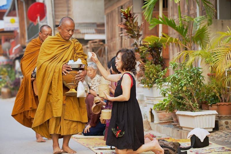 Les gens offrent le riz collant aux moines bouddhistes pendant le matin en Chiang Khan, Thaïlande photographie stock libre de droits