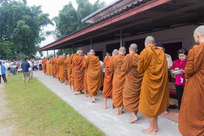 Les gens ont mis des offres de nourriture dans l'aumône de moine bouddhiste roulent pour faire images libres de droits