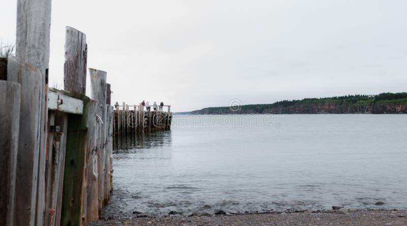 Les gens pêchant à l'extrémité d'un dock dans le printemps Littoral de Nova Scotia en juin photographie stock