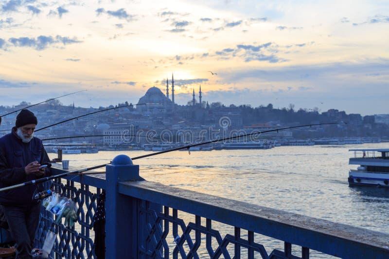 Les gens pêchant sur le pont de galata avec le fond de mosquée de suleymaniye pendant le coucher du soleil, Istanbul photos libres de droits
