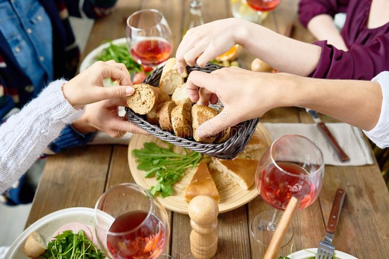 Les gens passant le pain au Tableau de dîner images libres de droits