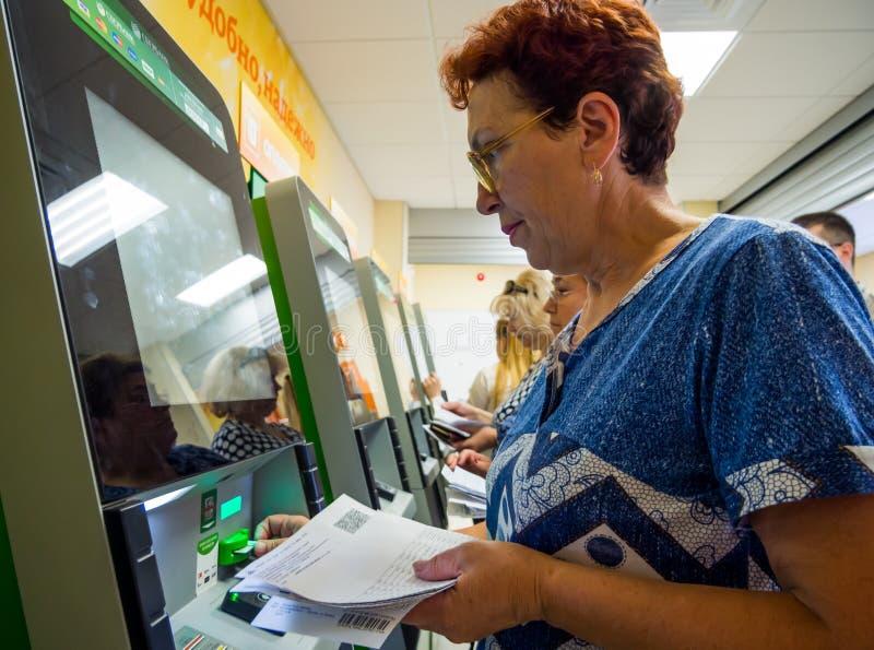 Les gens payent le logement et les services communaux dans des terminaux de libre service image libre de droits