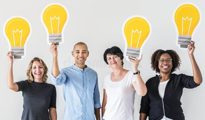 Les gens portant des icônes d'ampoule image stock