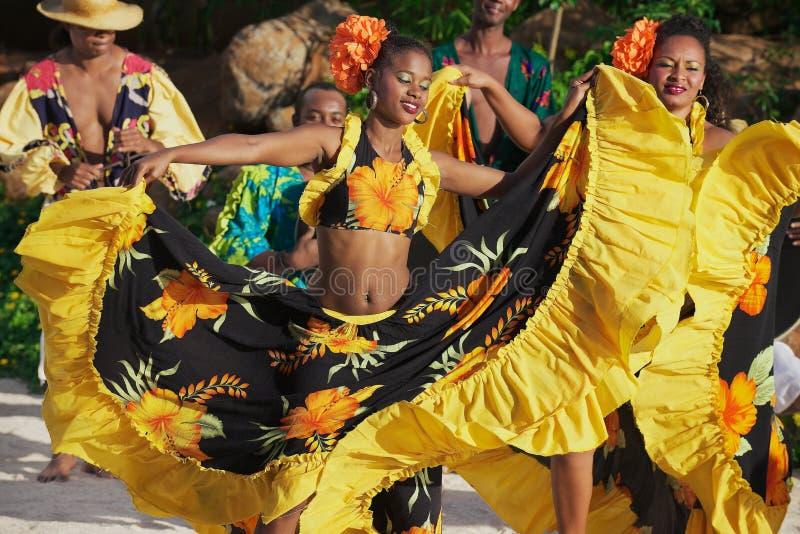 Les gens portant les robes colorées exécutent la danse créole traditionnelle de Sega au coucher du soleil en Ville Valio, Îles Ma photos libres de droits
