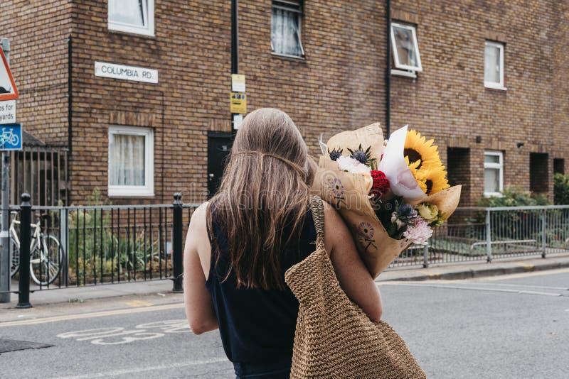 Les gens portent des plantes et des fleurs achetées au marché de fleur de route de Colombie, Londres, R-U photos stock