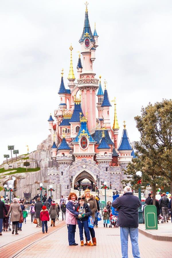 Les gens près du château dans le Disneyland Paris prennent la photo photographie stock