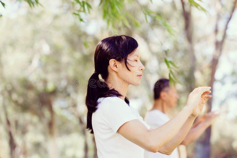 Les gens pratiquant le chi thaïlandais en parc photos libres de droits