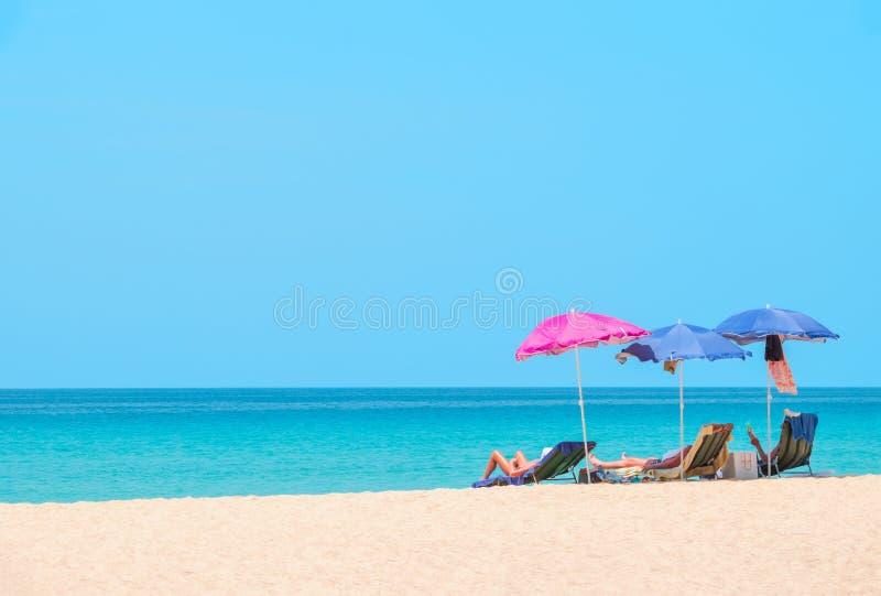 Les gens prenant un bain de soleil et détendant sur des chaises de plage images libres de droits