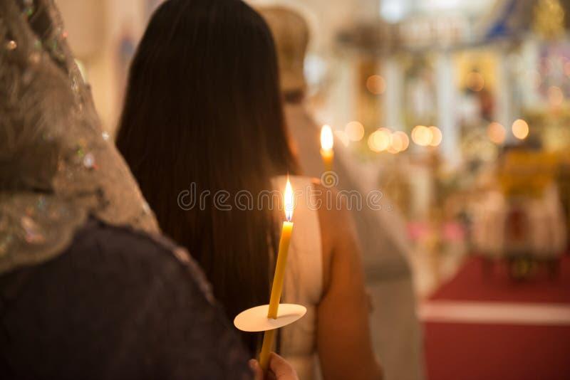 Les gens priant dans l'église avec des bougies dans les mains photographie stock libre de droits