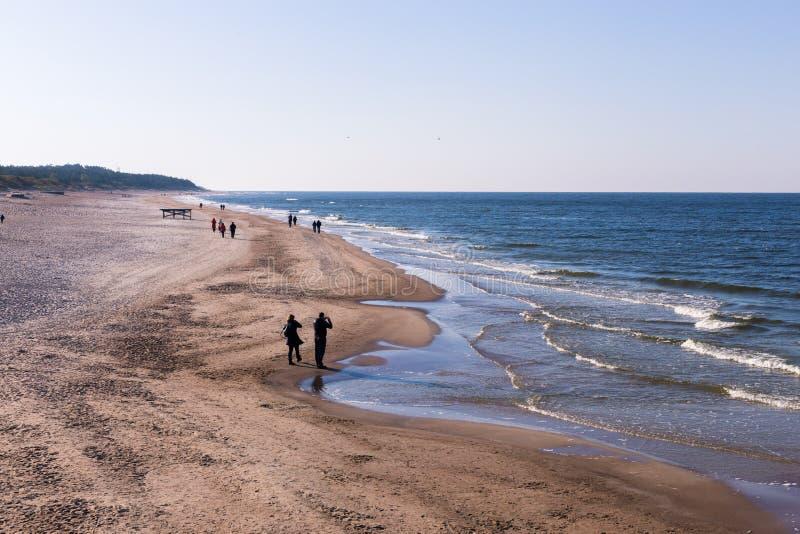 Les gens qui marchent sur le bord de la mer en automne image stock