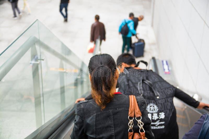 Les gens qui marchent vers le bas sur l'escalator photos stock