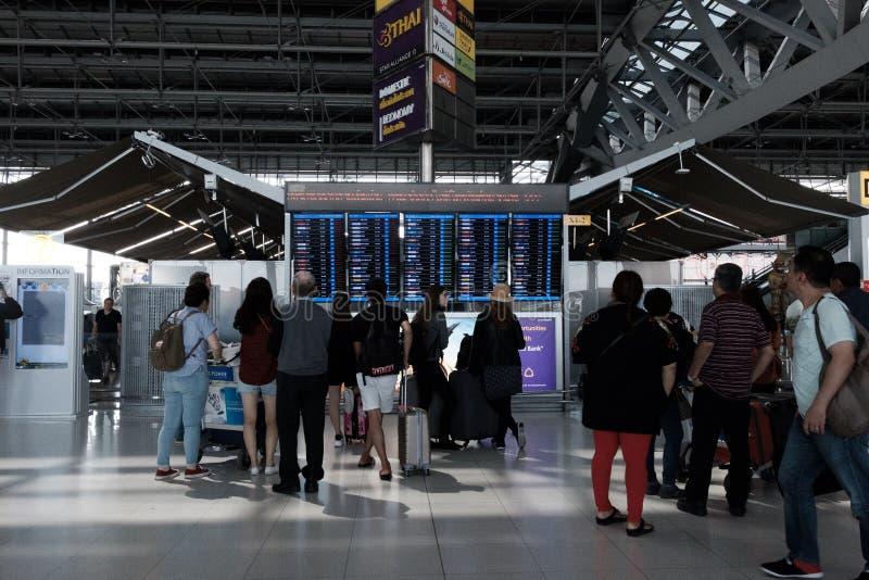 Les gens regardant le panneau d'affichage de vol l'aéroport de Suvarnabhumi photos stock