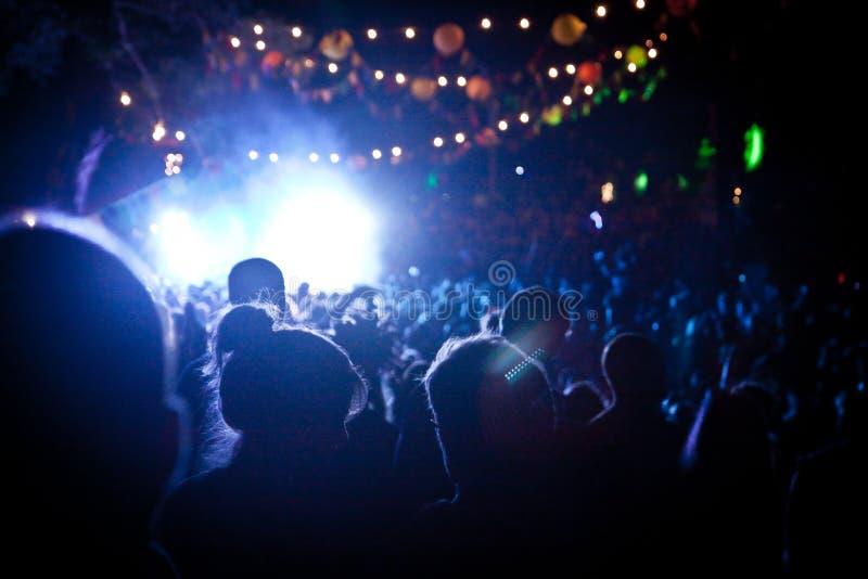 Les gens regardant une étape de festival la nuit avec l'éclairage de couleur photos stock
