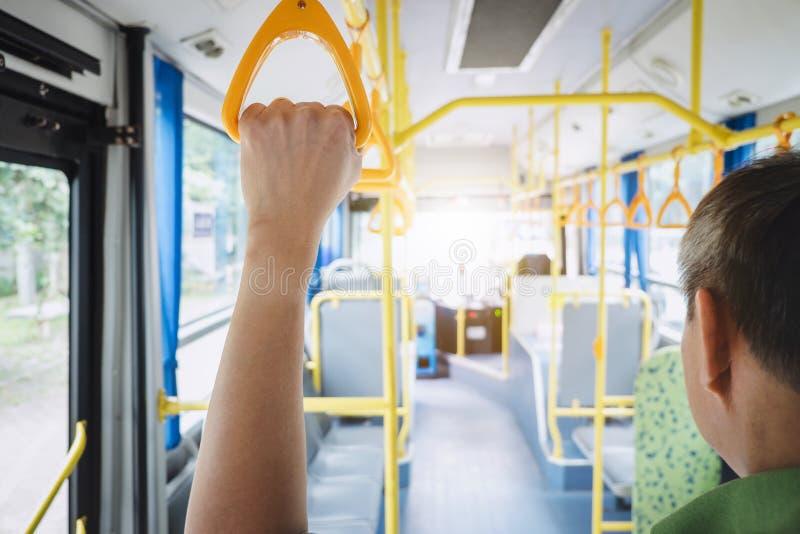 Les gens remettent tenir des poignées pour le passager debout dans le concept d'autobus, de transport, de tourisme et de voyage p photographie stock