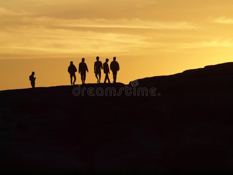 Les gens restant dans le coucher du soleil photo libre de droits