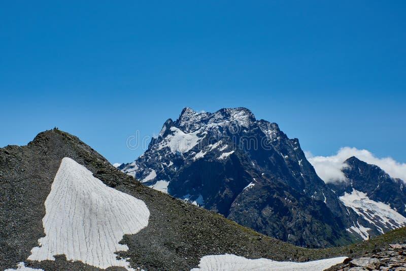 Les gens s'élevant jusqu'au dessus contre le contexte d'une gamme de montagne Dombay, Caucase du nord, Russie image stock