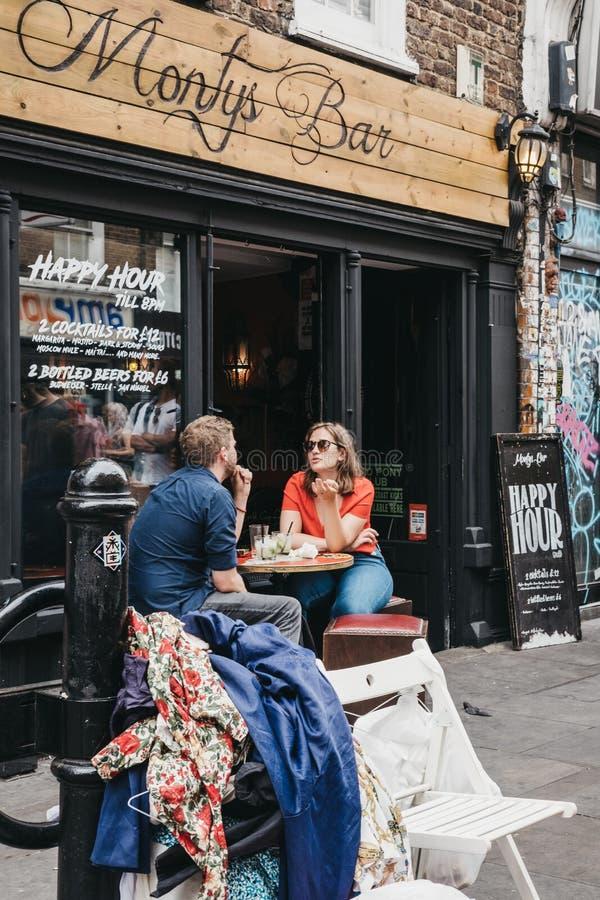 Les gens s'asseyant aux tables extérieures de la barre de Monty dans la ruelle de brique, Londres, R-U photos stock