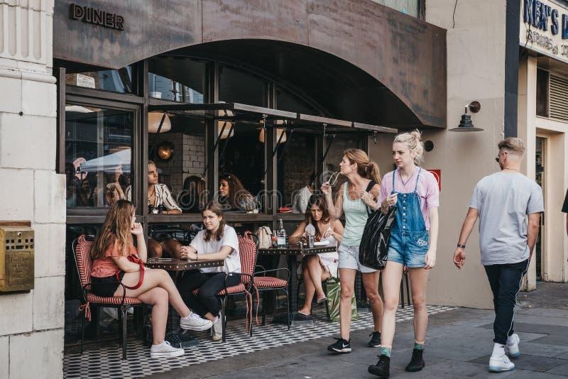 Les gens s'asseyant aux tables extérieures du wagon-restaurant dans la route mars de Portobello photographie stock