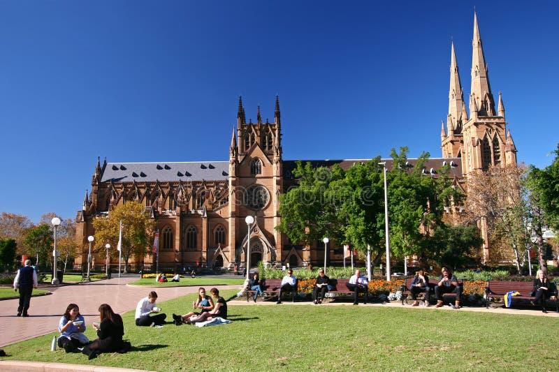 Les gens s'asseyant et détendant sur l'herbe et les bancs dans Hyde Park et l'église gothique en pierre rouge historique de renai photo stock