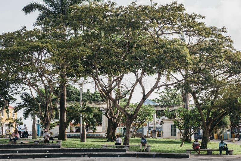 Les gens s'asseyant sur les bancs dans la place de l'indépendance, Bridgetown, Barbade image stock