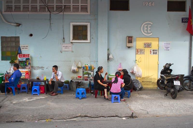 Les gens s'asseyant sur de petites chaises en caf? de rue photographie stock libre de droits
