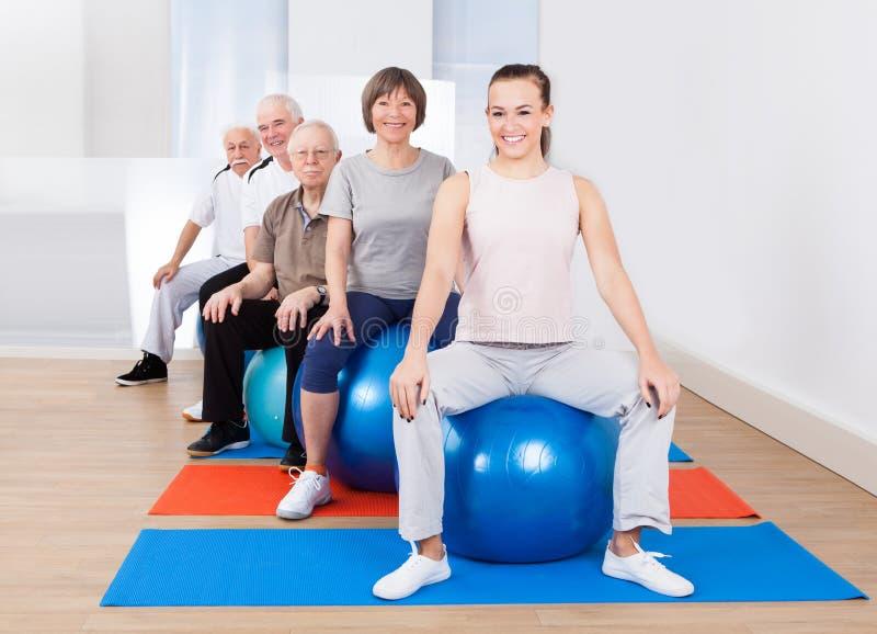 Les gens s'asseyant sur des boules de forme physique dans la classe d'exercice photos libres de droits