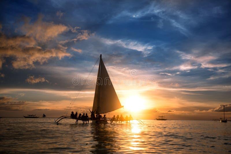 Les gens s'asseyant sur le voilier à l'océan et regardant le coucher du soleil photographie stock