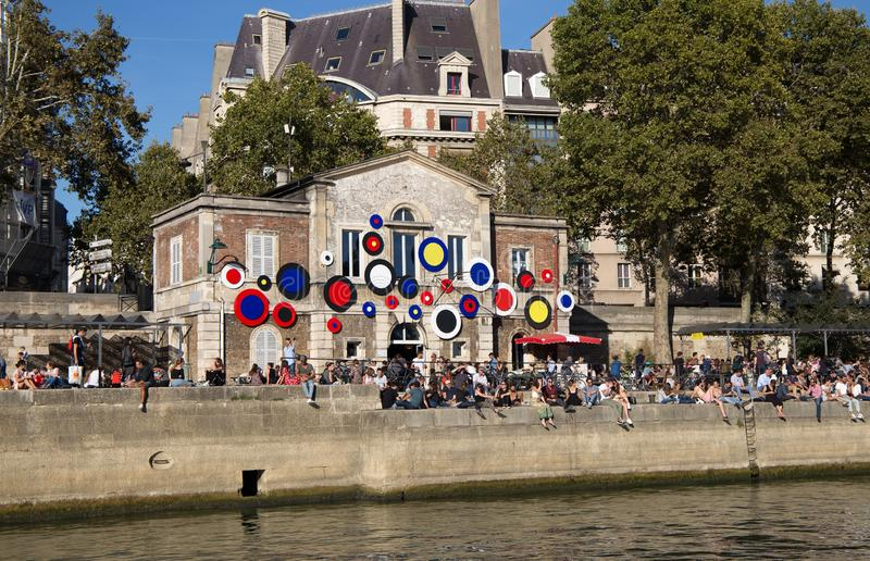 Les gens s'asseyent le long des rivages de la rivière la Seine dans un jour ensoleillé à Paris, France image libre de droits