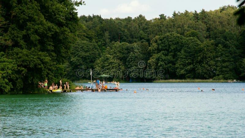 Les gens se baignant dans un lac pendant l'après-midi images libres de droits